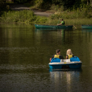 Couple in a boat and man in canoe on lake