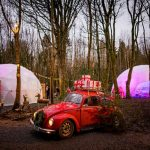 Domes and VW car with fairy lights and presents during Christmas event